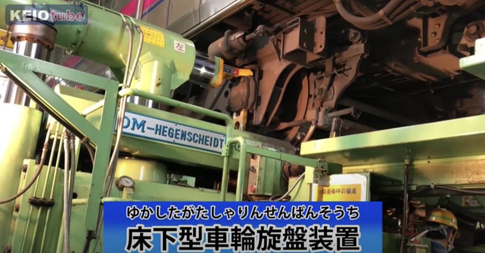 電車の車輪を削って形を整える床下型車輪旋盤装置(KEIOtube「若葉台車両基地オンラインツアー」場面)